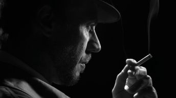 videoblocks-confident-noir-detective-smoking-a-cigarette-he-turns-and-looks-at-the-camera_h6bnhcosf_thumbnail-full01